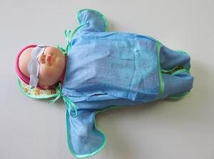 Новорожденный во фланелевом конверте с полупрозрачными для синего света окнами со стороны спины и груди.
